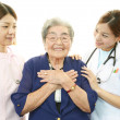 Stock Photo: Smiling Asimedical staff with old woman