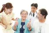 Smiling Asian medical staff with old women — Stok fotoğraf