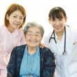 Smiling Asian medical staff with old woman — Stockfoto
