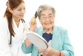 Doctor en medicina asiática sonriente y mujer senior — Foto de Stock