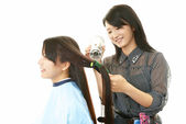 Hairdresser drying customer's hair with hair dryer — Stock Photo