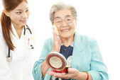 Smiling Asian doctor and senior woman — Stock Photo