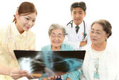 Medical staff with senior women — Stock Photo