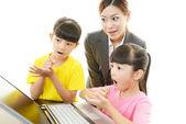 Smiling girls using a laptop — Stock Photo