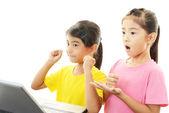 улыбаясь девочек, используя ноутбук — Стоковое фото