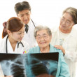 Smiling Asian medical staff with old women — Stockfoto
