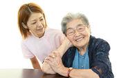 Friendly nurse cares for an elderly woman — Stock Photo