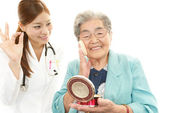 Smiling medical doctor and senior woman — Stock Photo