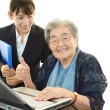 Young woman helping an elderly lady use a computer — Stock Photo