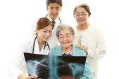 Smiling Asian medical staff with old women — Stock Photo