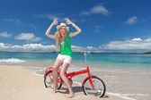 молодая женщина, езда на велосипеде на пляже — Стоковое фото