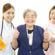 Asian medical staff with old woman — Stock Photo