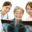 Smiling Asian medical staff with old woman — Foto de stock #31733485