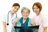 Smiling Asian medical staff with old woman — Foto Stock