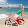 Young woman riding a bike on the beach — Stock Photo
