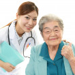 Smiling Asian medical doctor and senior woman — Stock Photo #32113567