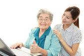 Old woman enjoys computer — Stock Photo