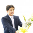 Stock Photo: Smiling businessmwith flower