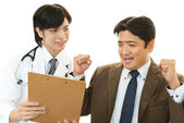 Smiling Asian medical doctor and patient — Stock Photo