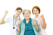 Asian medical doctors and senior woman — Stock Photo