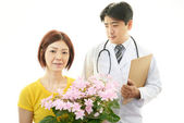Asian medical doctor  and woman holding flower — Stock Photo