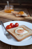 Toast with fried egg in the shape of heart and cherry tomatoes — Stock Photo