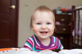 Little smiling baby girl standing near the bed — Stock Photo