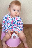 小女婴,正坐在粉红色的锅和从一瓶喝水 — 图库照片