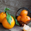 Oranges with leaves and tangerines  on wooden table — ストック写真