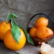Oranges with leaves and tangerines  on wooden table - Stock Photo