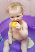 Small smiling baby girl washes in a baby bath with water spray — Stock Photo
