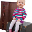 Small baby girl sitting on the old wooden box with a suitcase, w — Stock Photo