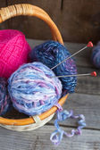 Woolen clews for knitting with knitting needles in a basket — Foto Stock
