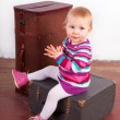Small baby girl sitting on the old wooden box with a suitcase — Stock Photo