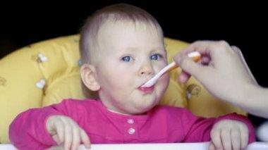 Baby flicka äter betor rot soppa och skakar huvudet i olika riktningar — Stockvideo