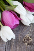 A bunch of fresh tulips flowers on a rustic wooden background — Stock Photo