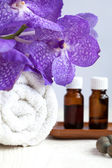 Spa still life with blue orchid flower, towel and aromatic oils — Стоковое фото