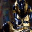 Statue of Anubis with the mummy of the deceased on a black backg — Stock Photo