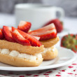 Fresh cream eclairs with whipped cream and strawberries and cup — Stock Photo