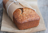 Banana bread in the baking paper on the wooden table — Stock Photo