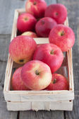 Red apples in a basket on the wooden table — Stock Photo