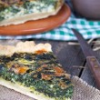 Royalty-Free Stock Photo: A piece of homemade pie with spinach and cheese on a wooden tabl