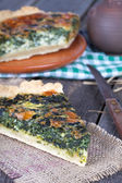 A piece of homemade pie with spinach and cheese on a wooden tabl — Stock Photo