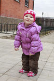 Little cute girl on a walk in the spring in a jacket and knitted — Stock Photo