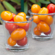 Red and yellow cherry tomatoes in glasses — Stock Photo