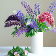 Still life, a white vase with purple and pink lupine and Pink fl — Stock Photo