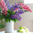 Still-life, white vase with purple and pink lupine on the table, — Stock Photo