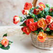 Beautiful bouquet of roses in basket on wooden table, selective — Stock Photo