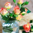 Beautiful bouquet of roses in glass on wooden table , selective — Stock Photo