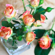 Beautiful bouquet of roses in glass on wooden table, selective f — Stock Photo